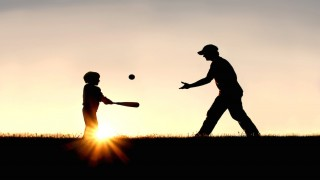 A silhouette of a father and his young child playing baseball outside, isolated against the sunsetting sky on a summer day.